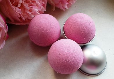 three pink bath fizzies scented in bubblegum placed on the table next to pink peonies