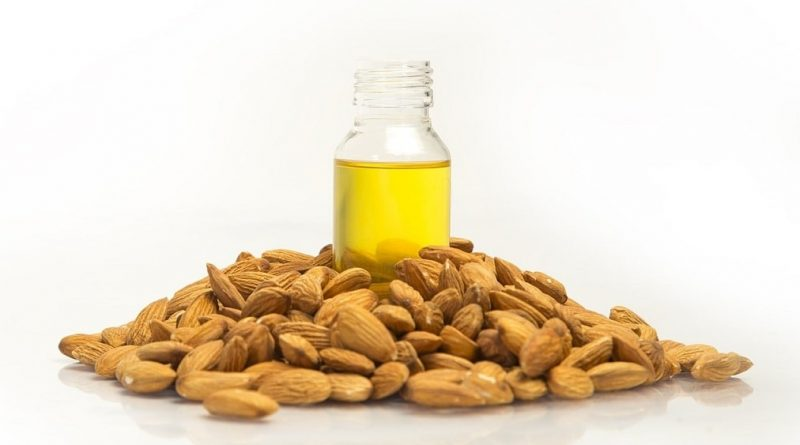 Almond oil with almond nuts around itt