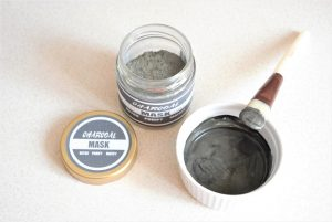 dry mix of DIY charcoal mask in a jar with a dark grey charcoal printable label on the jar. Next to it a bowl with a dry charcoal mask mixed with water and a brush
