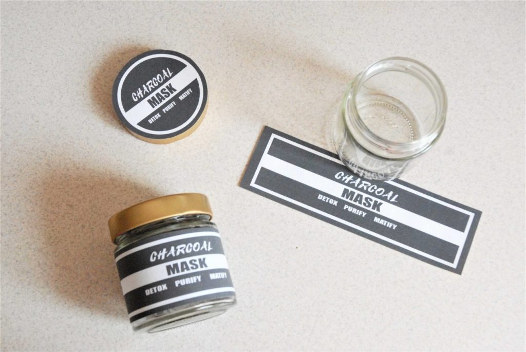 charcoal mask labels displayed on the jar with diy charcoal and clay mask. next to it empty jars and printed mask labels