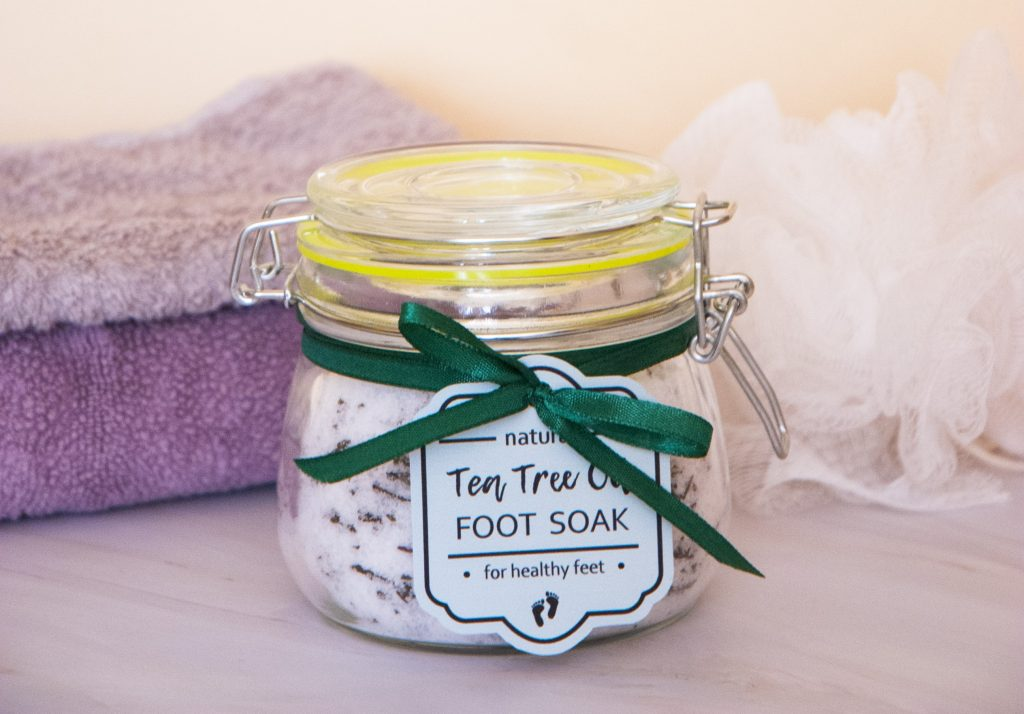 Homemade tea tree oil foot soak with epsom salt in the jar with a green gift tag