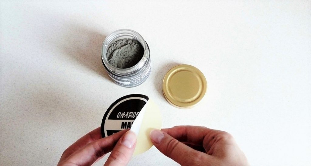sticking printed charcoal mask label on the jar