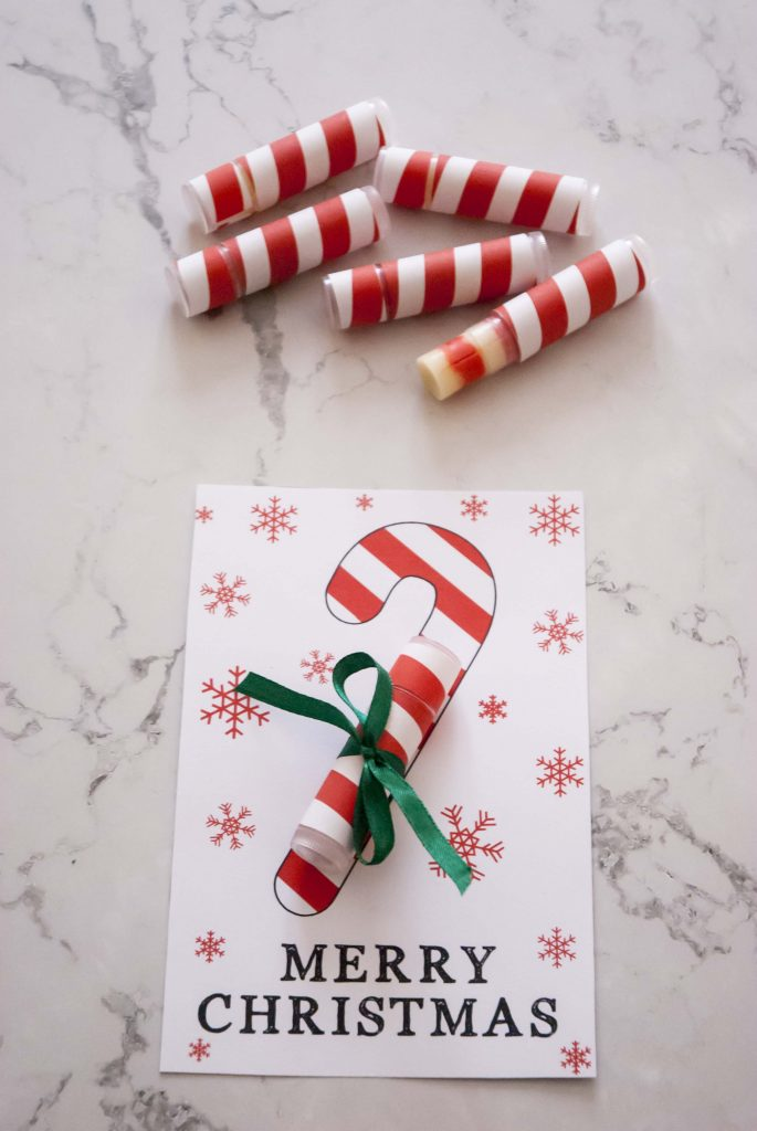 diy candy cane lip balms with red white labels next to diy lip balm christmas card