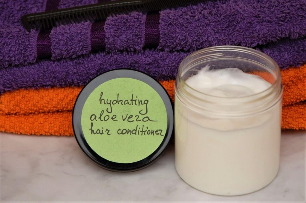 A jar with homemade hair conditioner next to towels