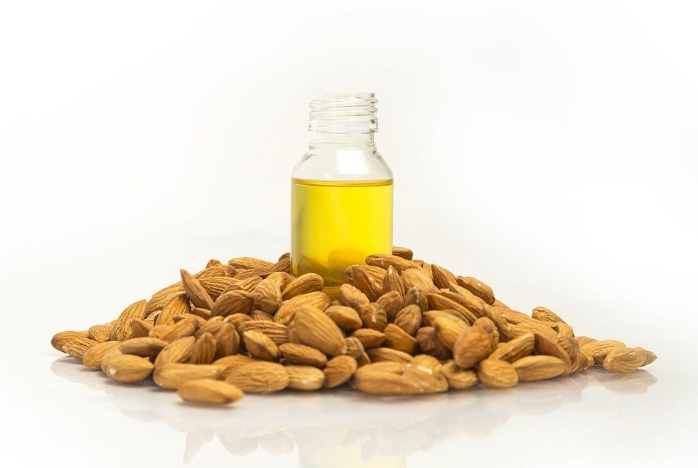 bottle of sweet almond oil surrounded by almonds