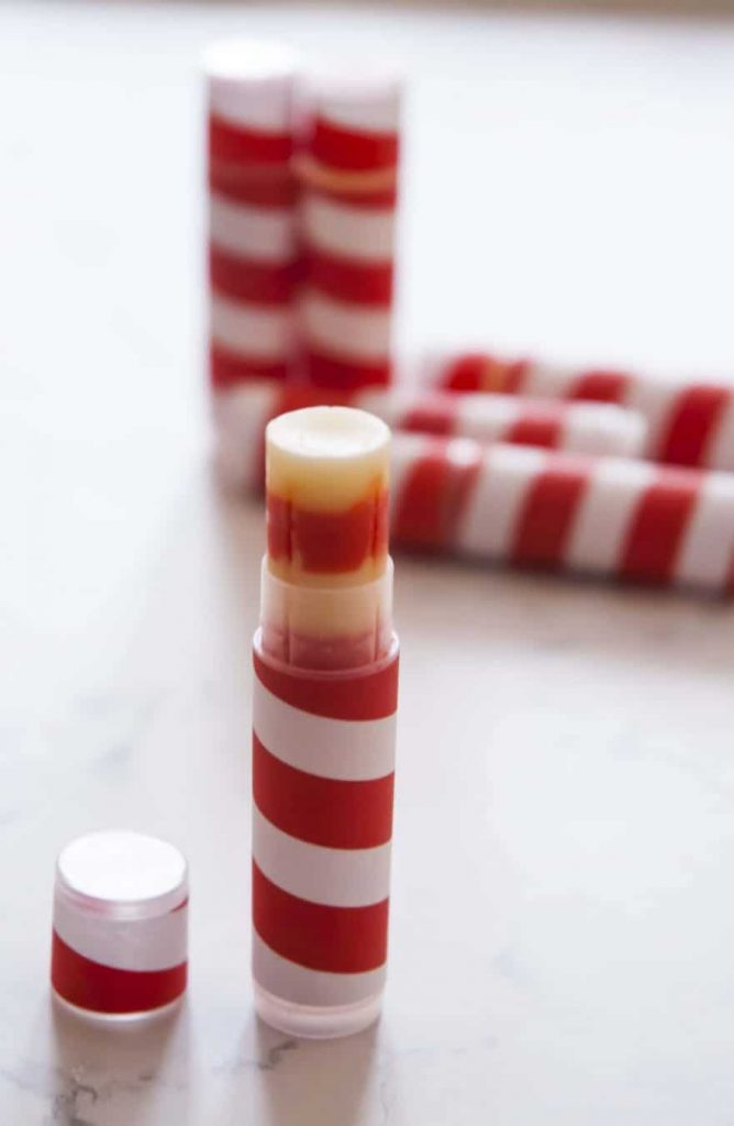 Six DIY candy cane scented lip balms on the table. All lip balms wrapped in red white stripe labels to resemble candy cane
